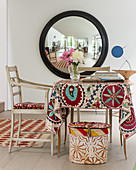 Large convex mirror with old textiles adding colour