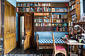 Wooden bookshelves above daybed with desk in study