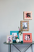 Pictures in decorated frames on and above console table