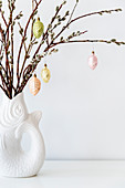 Pastel baubles hung from willow branches in fish-shaped vase