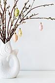 Anhänger in Pastell an Weidenzweigen in einer Vase in Fischform