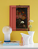 Arrangement of old picture and frame partially painted over and white vases