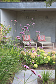A view over a bed of hydrangeas to a terrace with loungers