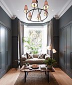 Kleines Wohnzimmer mit grauen Wandschränken und Sofa im Erker