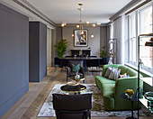 Green sofa, dining area and fitted cupboards in elegant interior