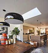 Black ceiling lamps above dining table in front of open-plan kitchen