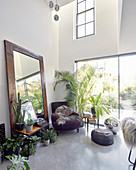 Floor-standing mirror and collection of houseplants in dining room with concrete floor
