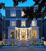 Klassisches Haus im Englischen Stil mit Erkern, beleuchtet am Abend