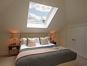 Bed below skylight with view of cloudy sky