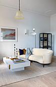 Geschwungenes Sofa und weißer Couchtisch im Wohnzimmer