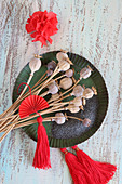 Dried poppy seed heads, poppy seeds and red tassels