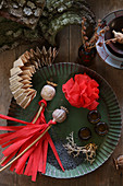 Dried poppy seed heads and red tassels on crepe paper