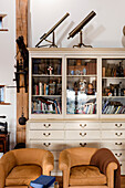 18th century telescopes on top of glass fronted cabinet with antiques and pair of suede armchairs barn conversion