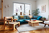 A blue upholstered sofa, a wooden coffee table and a designer chair