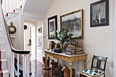 Neatly stacked books on neoclassical gilded table in front hall with hand painted, lacquered 19th century French chairs