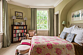 Pink floral quilted cover on bed in Victorian home with vintage bookcase