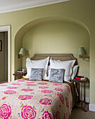 Pink floral quilted cover on bed in Victorian home