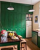 Fresh lemonade on table in bright green kitchen