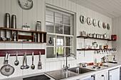 Küchenutensilien auf Regalen und Innenfenster in einer renovierten Küche mit Holzverkleidung