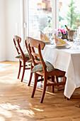 Gedeckter Tisch mit Stühlen in hellem Esszimmer
