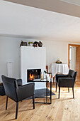 Leather armchairs and glass table in front of fireplace in light room