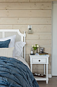 Blue quilt on double bed with wood cladding and glass wall light
