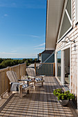 Large wooden decking with casual chairs with stripy blue and white cushions.
