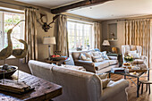 Neutral sofas with wall mounted antlers and bird ornaments in restored 16th century farmhouse