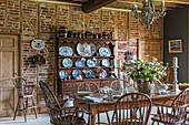 Holztsich mit Stühlen und Anrichte mit Tellerboard im restaurierten Bauernhaus