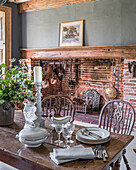 Glassware and plates on antique table with restored 16th century inglenook fireplace