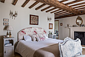 Emboidered folk art above double bed with floral headboard in 16th century farmhouse renovation