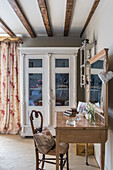 Glass fronted cabinet with floral curtains and wooden dressing table with wicker chair in 16th century farmhouse renovation