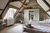 Twin beds and decorative wardrobe in roof space of restored 16th century farmhouse