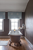 Freestanding bath with light blue emboidered curtains at window in restored 16th century farmhouse