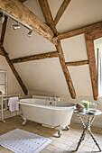 Freestanding bath below timber framed attic in restored 16th century farmhouse