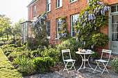 Folding table and chairs in garden of brick 16th century farmhouse