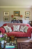 Couchtisch, pinkfarbenes Sofa mit Kissen und Bilder an der Wand im Wohnzimmer