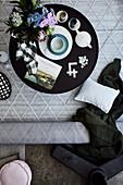 Schwarzer Beistelltisch mit Teegeschirr, Blumen, Buch und Scrabble