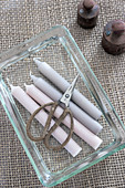 Pastel-coloured candles and scissors in glass dish