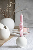 Artistically twisted candles on table set for Easter meal