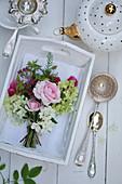 Kleiner Strauß aus Rosenblüten, Hortensie und Spierstrauch auf Holztablett