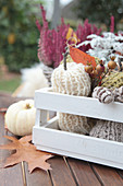 Knitted pumpkin decorations, autumn leaves and white squash