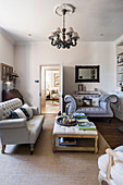 Buttoned sofas and ottoman in muted living room with coir matting