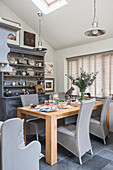 Pendant lights and closed Venetian blinds with wooden table and kitchen dresser