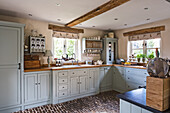 Light blue fitted kitchen with cobblestone flooring