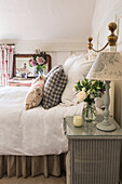 Lamp and bouquet of roses on bedside table next to wrought-iron bed in bedroom