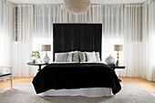 Double bed with screen as bed headboard in bedroom with curtain all around