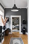 Hallway with grey walls and wooden floorboards