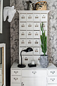 White chest of drawers with apothecary cupboard on top used as bedside table