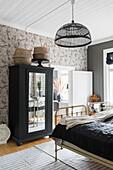 Schwarze Kleiderschrank mit Spiegeltür und zwei alte Eisenbetten im Gästezimmer